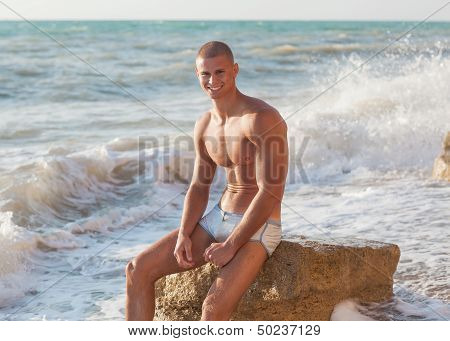 Portrait Of A Handsome Young Muscular Man In Swimtrunks With Water Ocean Background