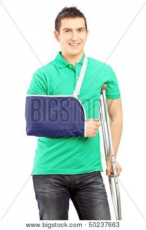 Smiling male with broken arm and crutch isolated on white background
