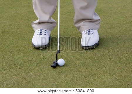 Golf club and ball on tee grass