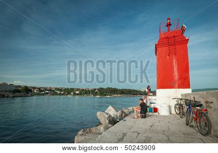 KRK, CROATIA - MAY 4, 2013: Fishermen in harbour at red lighthouse on May 4, 2013 in Krk, Croatia. Ancient Krk town, is among the oldest cities in Adriatic, continuously inhabited since Roman times.