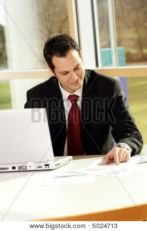 Business Man Is Working On A Table With A Laptop