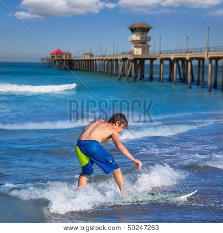 Boy surfer surfing waves on Huntington beach pier California [ photo-illustration]