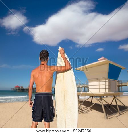 Boy surfer back rear view holding surfboard on Huntington beach lifeguard house [ photo-illustration]