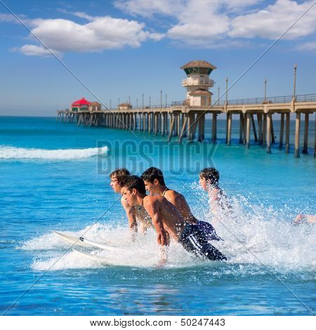 Teenager surfers surfing running jumping on surfboards at Huntington beach pier California [ photo-illustration]