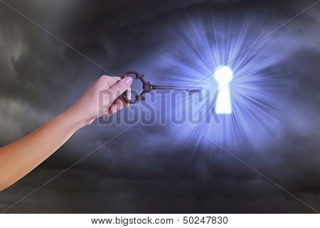 Close up image of human hand inserting key in key hole