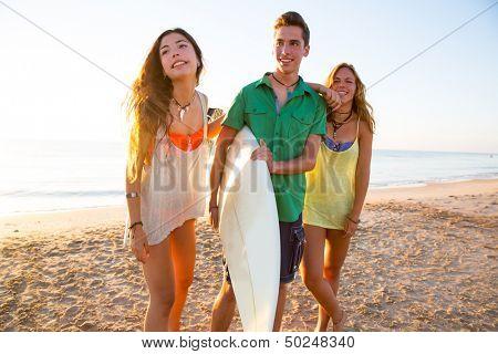 Surfer girls with teen boy walking on beach shore high key