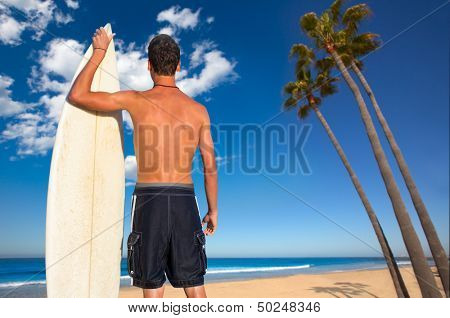 Boy surfer back rear view holding surfboard on California palm trees beach [ photo-illustration]
