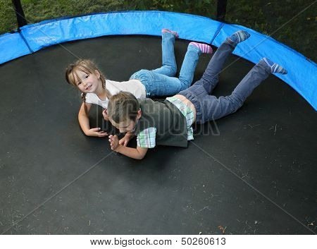 Two funny kids on a outdoor trampoline.