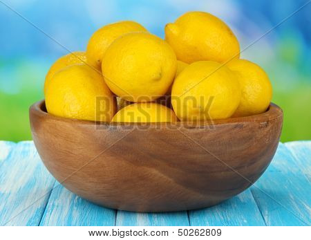 Ripe lemons in bowl on table on bright background