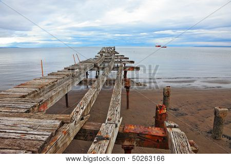 Old dilapidated pier in the Strait of Magellan. Corroded bearings and collapsed wooden flooring