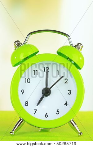 alarm clock on table on light background
