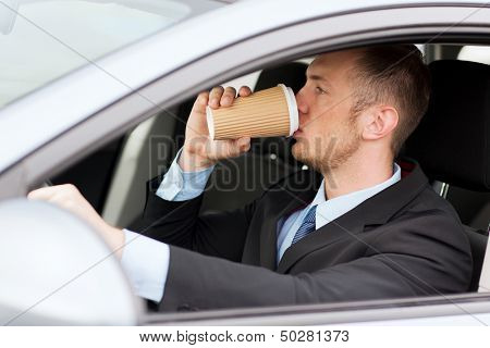 transportation and vehicle concept - man drinking coffee while driving the car
