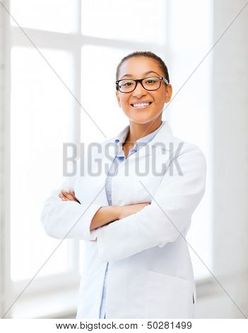 healthcare and medical concept - smiling african female doctor in hospital