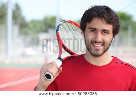 Tennis player stood with racket over shoulder