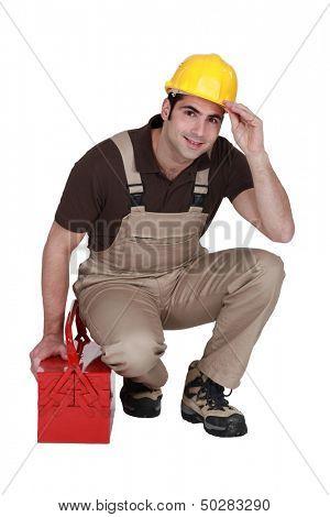 Trabalhador da construção civil posando com sua caixa de ferramentas e usando um capacete