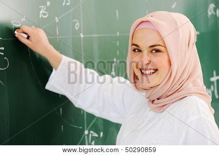 Arabic Muslim teenage student inside the high school classroom posing on board