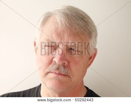 older man has a distrusting look