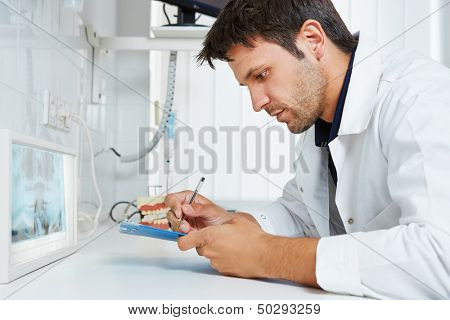 Dentist with x-ray image of teeth taking some notes in his dental practice