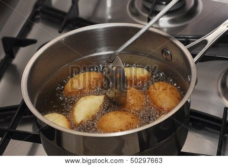 Doughnuts Frying In A Boiled Oil Stirring By Skimmer
