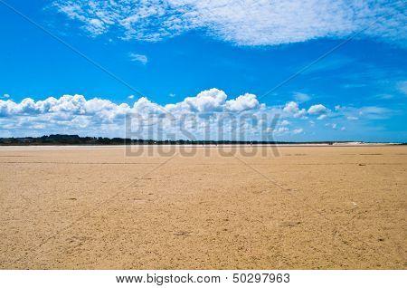 Grande praia de areia com céu azul durante a maré em o Bretagne na França