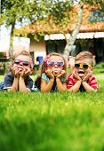 image of fleet  - Cheerful kids laying on a grass - JPG