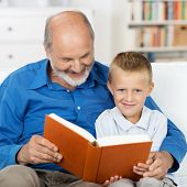 foto of babysitting  - Grandfather reading to his small grandson who is looking up to smile at the camera as they sit arm in arm close together on a sofa in the living room - JPG