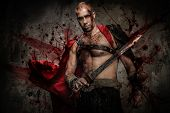 stock photo of legion  - Wounded gladiator with sword covered in blood - JPG