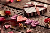 picture of rose flower  - Word Love with heart shaped Valentines Day gift box on old vintage wooden plates - JPG