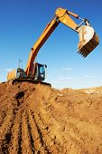 stock photo of risen  - loader excavator machine doing earthmoving work at sand quarry - JPG