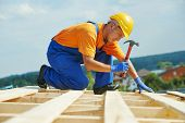 stock photo of labor  - construction roofer carpenter worker nailing wood board with hammer on roof installation work - JPG