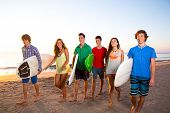 Surfer teen boys girls group walking on beach at sunshine sunset