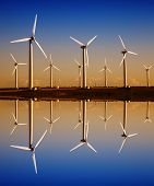 stock photo of wind-turbine  - white wind turbines with digital water reflection - JPG