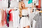 foto of boutique  - Fashionable young woman shopping in a clothing store - JPG