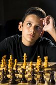 pic of 11 year old  - An 11 year old boy thinking about his next move during a chess game.