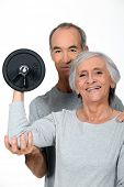 foto of elliptical  - Older couple working out with weights - JPG