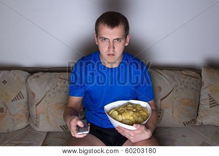 Young Man Sitting In Living Room And Watching Tv With Chips