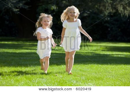 Two Pretty Young Girls Running Through A Sunlit Green Park