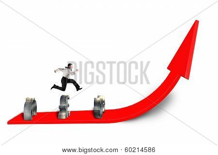 Businessman Jumping Over Money Symbol On Growing Red Arrow