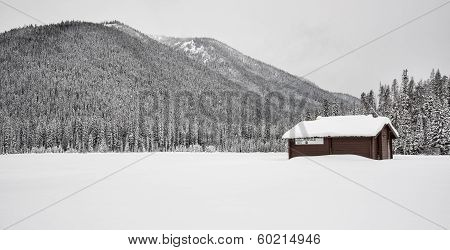 Lone Building Covered In Snow And Mountains
