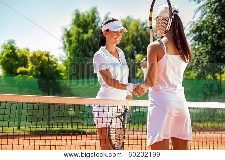 Women handshaking after playing a tennis match