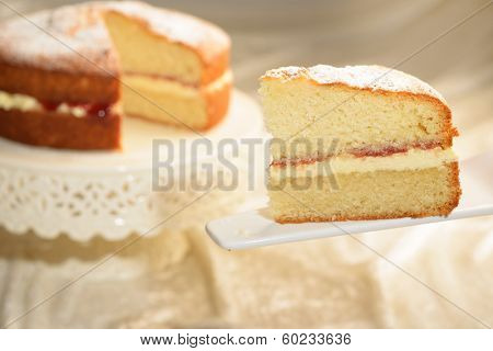 A slice of Victoria sponge cake with cut cake in the background