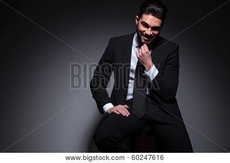 portrait of a seated young fashion man smiling for the camera while touching his beard. on a dark background
