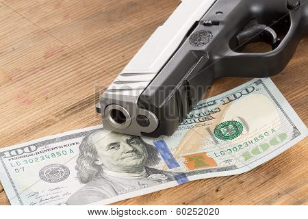 Muzzle Of A Gun With A 100 Dollar Bill