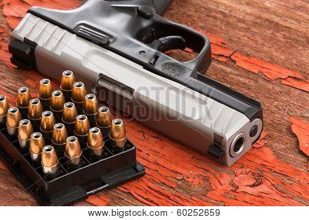 Close Up Of A Handgun And Rack Of Ammunition