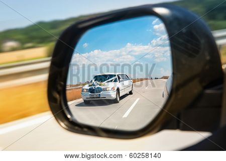 Reflection of wedding car in the rearview mirror