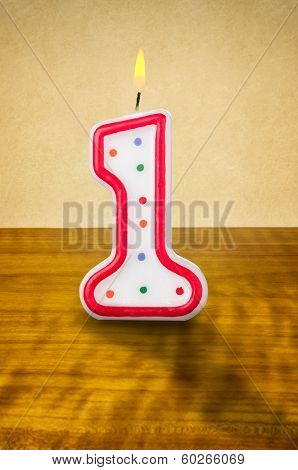 Burning birthday candle number 1 on a wooden background