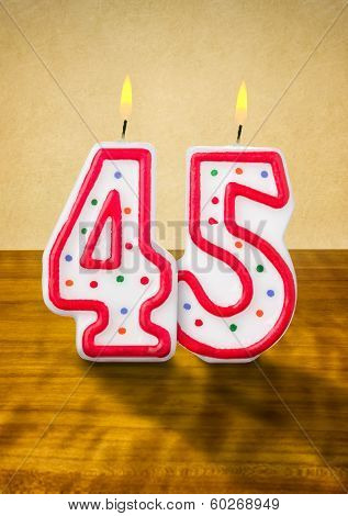 Burning birthday candles number 45 on a wooden background