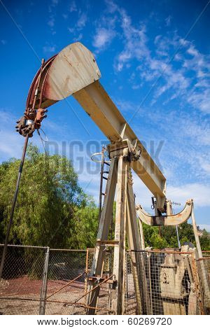 A horsehead pumpjack with a blue sky background with clouds