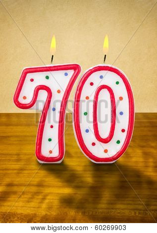 Burning birthday candles number 70 on a wooden background
