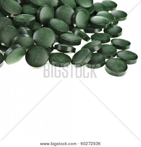 Tablets Spirulina  algae heap surface close up macro  top view, isolated on white background